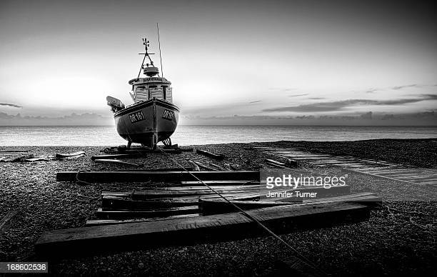 Black and white shot of a fishing boat on the shingle of Deal Beach, Kent at sunrise.