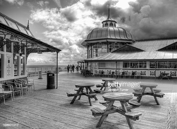 CONTENT] Black and white shot of an eating area on Llandudno pier Conwy North Wales