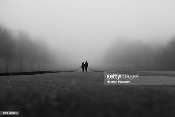 "Black and white shot of couple waking together along Windsor's ""long walk"" in thick fog with symmetry of misty trees."
