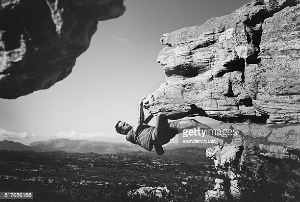Black and white shot of free climber hanging on rock