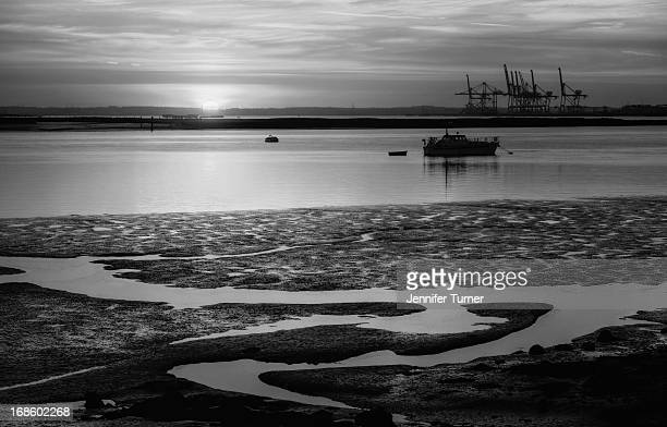 Black and white shot of sun just disappearing below the horizon. Taken at Queenborough on the Isle of Sheppey, Kent.