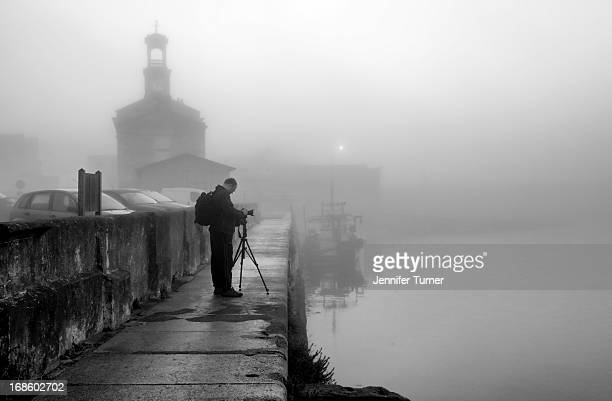 Black and white shot of sunrise over Ramsgate harbour in thick fog. Shot of photographer setting up for a shot