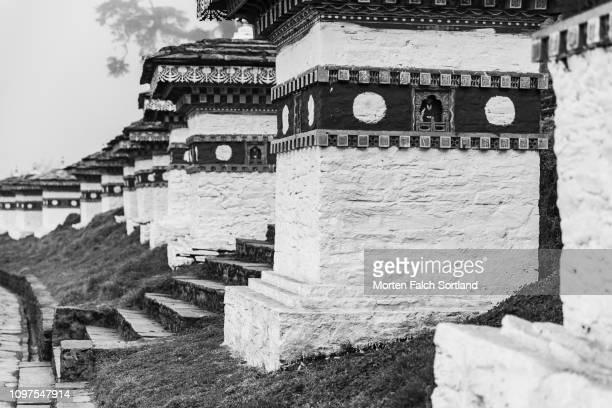 black and white shot of the chortens at the dochula mountain pass in dochula, bhutan springtime - dochula pass stock-fotos und bilder