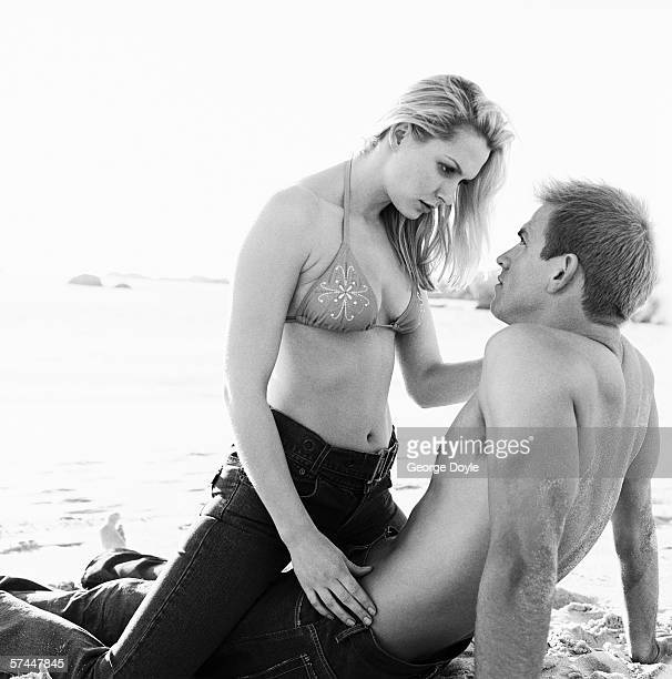 black and white side profile of a woman sitting on a man at the beach