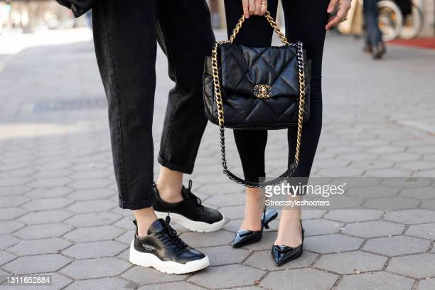 Black and white sneaker by Valentino Caravani as a detail of est Ager Model and Influencer Petra van Bremen and a black bag with gold details by...