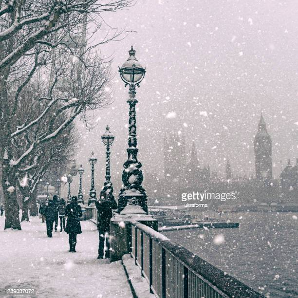 black and white - snow covered queen's walk at jubilee gardens in london at dusk - charming stock pictures, royalty-free photos & images