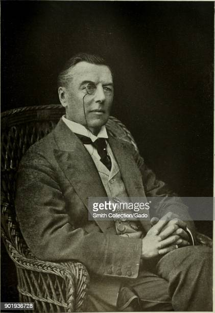 Black and white threequarter length portrait photograph of English statesman Joseph Chamberlain seated in a wicker chair with his hands clasped and...