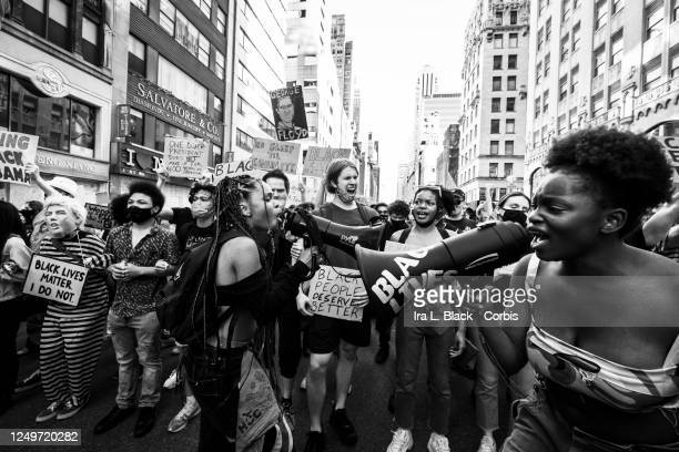 Black and white version of Kiara Williams and Livia Johnson, organization leaders for Warriors in the Garden scream into megaphones to lead a group...