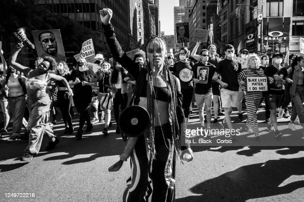 Black and white version of Livia Johnson, an organization leader for Warriors in the Garden holds a up her hand in a raised fist as she stands in...