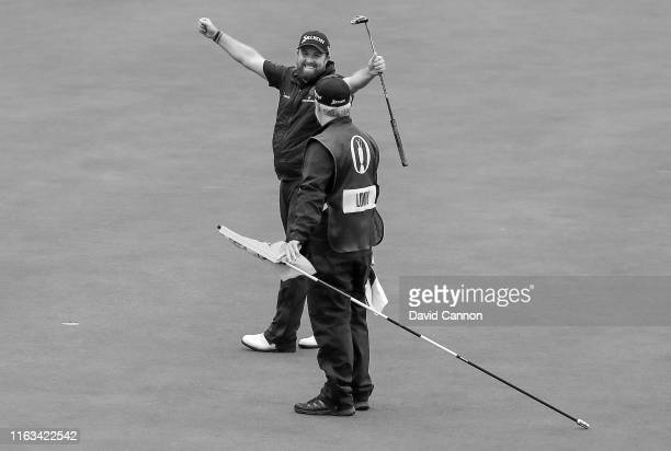 Black and white version of original colour image; Shane Lowry of Ireland celebrates with his caddie Brian Martin after holing the final putt on the...