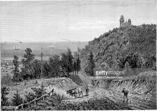 Black and white vintage print depicting several people and a horsecart traversing the road next to Beacon Hill, surmounted with a double lighthouse,...