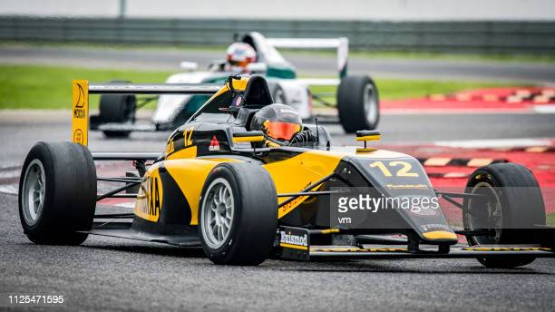 black and yellow formula race car on the track - race car driver stock pictures, royalty-free photos & images