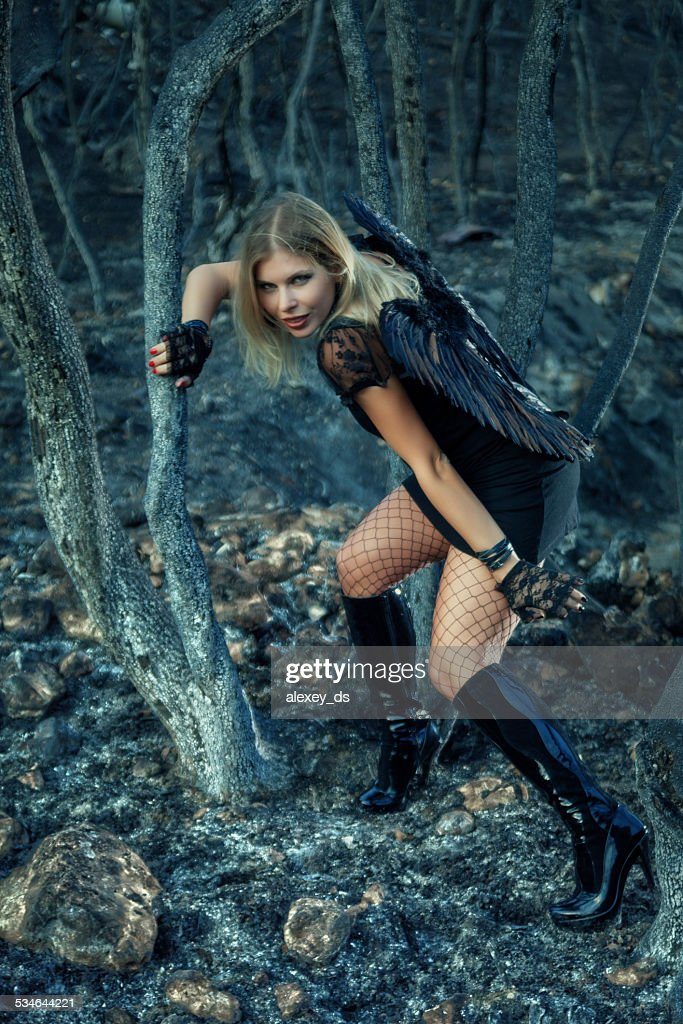 Black Angel in the burned forest : Stock Photo