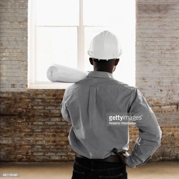 Black architect wearing hard-hat and holding blueprints
