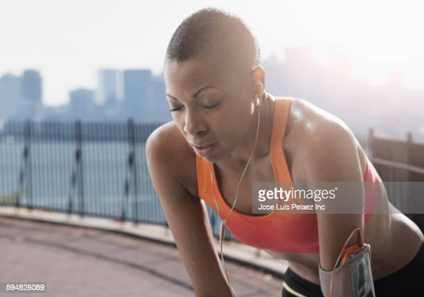 Black athlete resting on urban waterfront