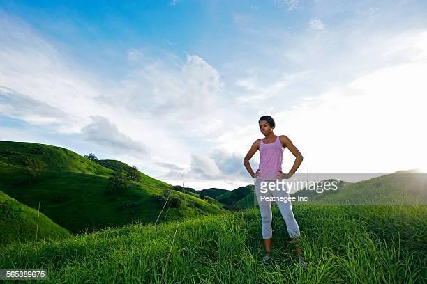 Black athlete standing on rural hillside