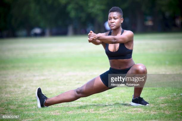 Black athlete stretching in park