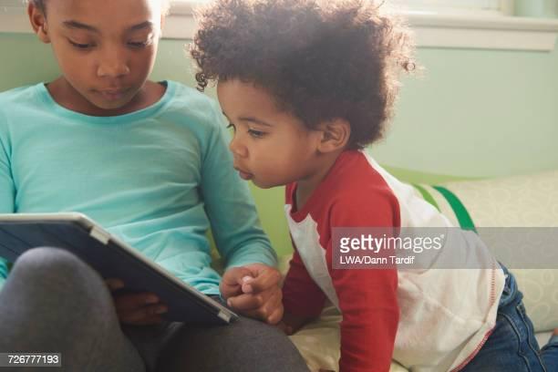 Black baby boy watching sister using digital tablet