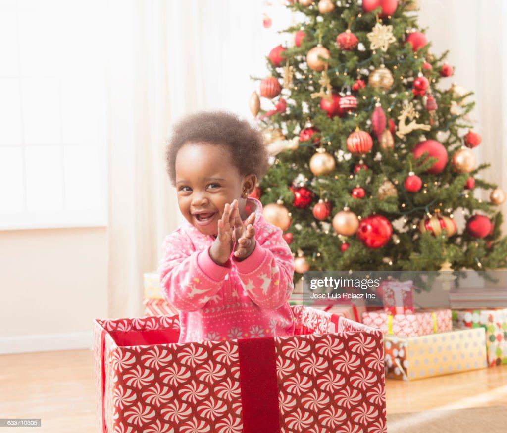 black baby girl playing in christmas gift box stock photo