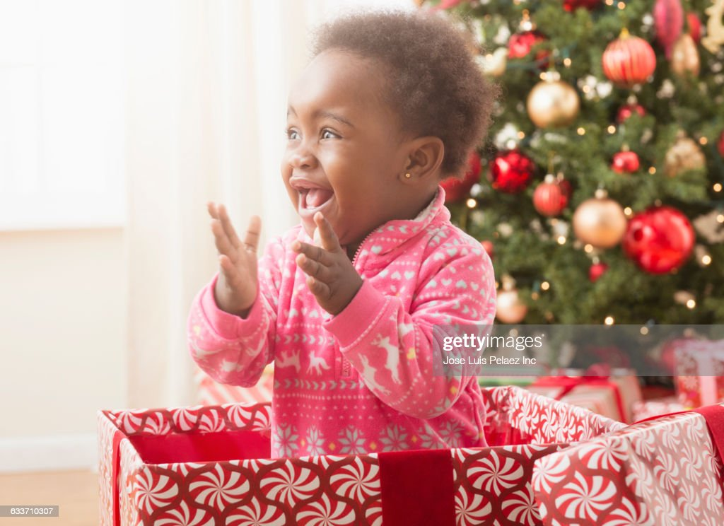 Black Baby Girl Playing In Christmas Gift Box Stock Photo | Getty Images