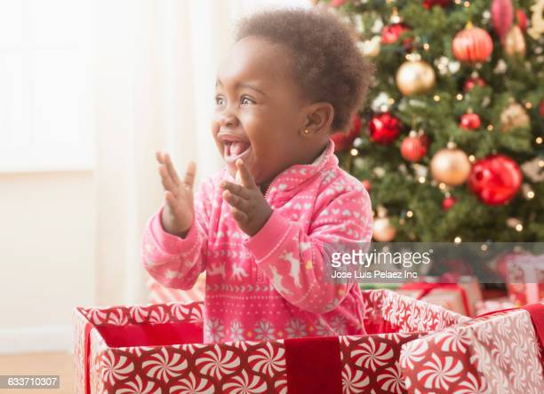 Black baby girl playing in Christmas gift box