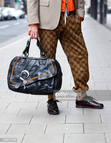 Black bag by Dior and dark brown sneaker by Gucci as a detail of stylist Bert Sterck during a street style shooting on March 19, 2021 in Dusseldorf,...