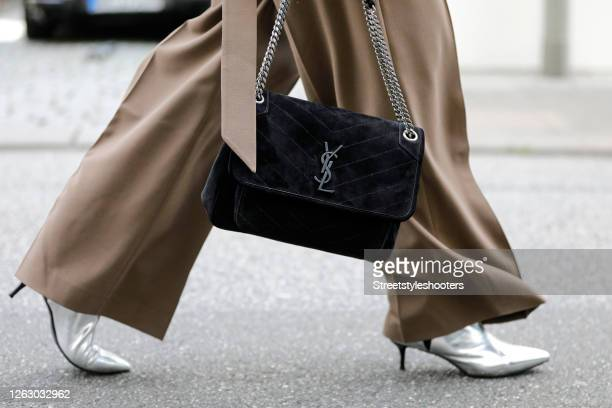 Black bag by Yves Saint Laurent and silver booties by Essential as a detail of best ager model and influencer Petra van Bremen during a street style...