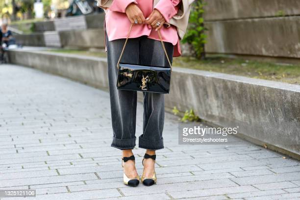 Black bag with gold details by Saint Laurent and gold and black two tone pumps with bows by Chanel as a detail of Influencer Gitta Banko during a...