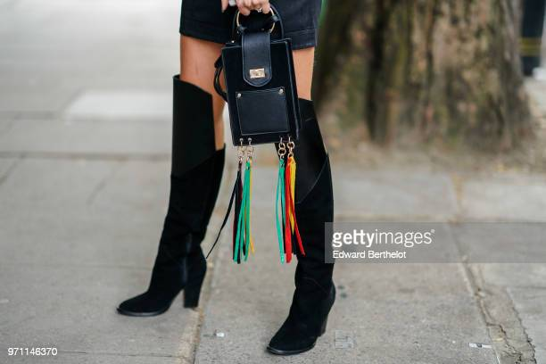 A black bag with multicolor fringes and high boots are seen during London Fashion Week Men's June 2018 on June 10 2018 in London England
