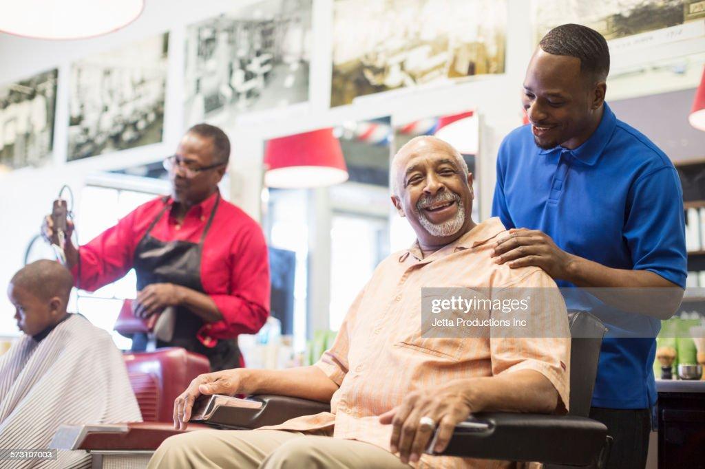 Black barber talking to customer in retro barbershop : Stock Photo
