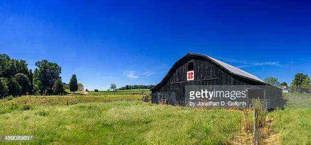 black barn in green field - eubank stock photos and pictures