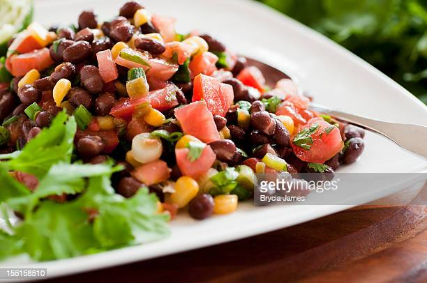 black bean salad on white plate siting horizontally on table - bean stock pictures, royalty-free photos & images