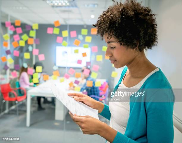 Black beautiful manager looking at documents very serious at the office