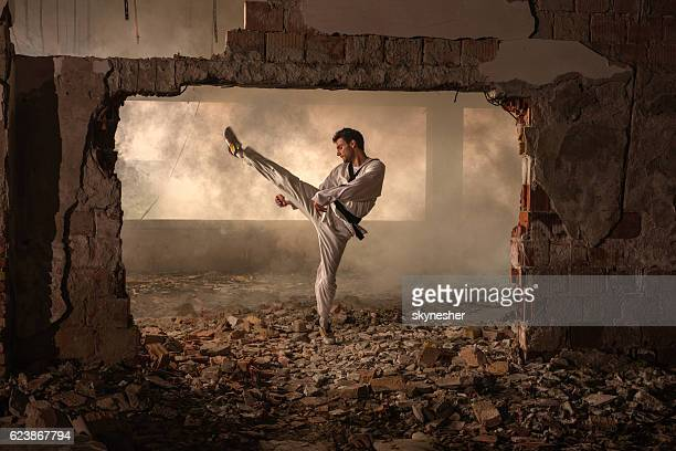 black belt martial artist practicing high kick among ruins. - kung fu stock photos and pictures