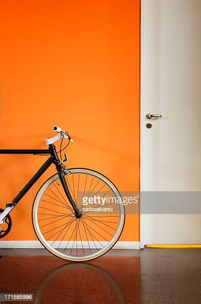 Black bicycle against an orange wall