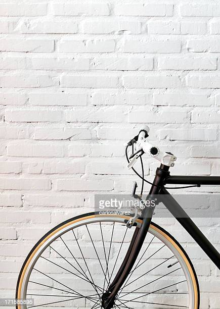 Black bicycle over a brick wall