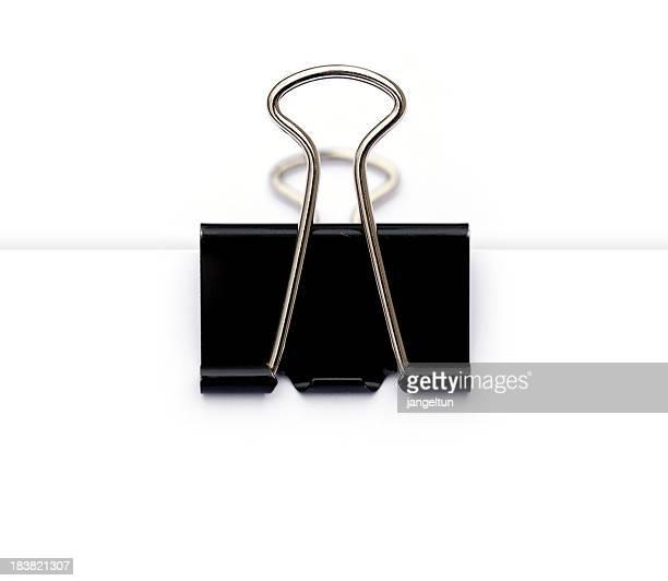 Black binder clip on paper stack