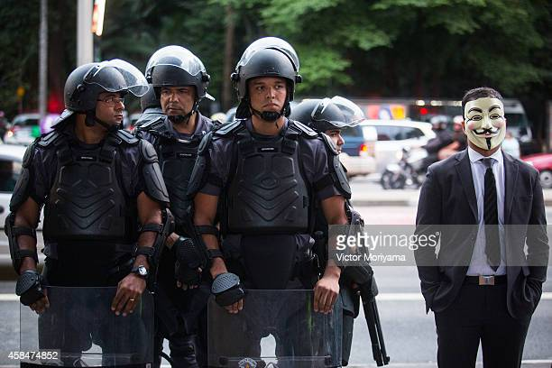 Black Bloc demonstrator stands next to a police officers during a protest against the lack of water that is affecting the entire state of Sao Paulo...