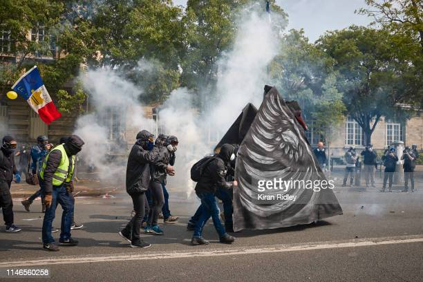 Black Block protestors hide from French Riot Police behind a Black Swan float during International Labour Day as demonstrations turn violent on May...
