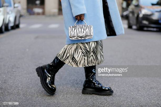 Black boots by Jeffrey Campbell and a black and white safari bag by Weat as a detail of influencer Lois Opoku seen during the Milan Women's Fashion...