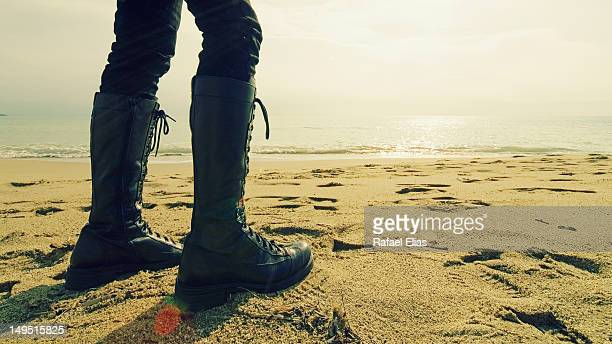 black boots on beach - black boot stock pictures, royalty-free photos & images