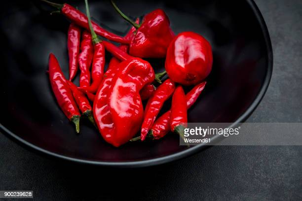 black bowl of various red chili pods - red chili pepper stock pictures, royalty-free photos & images