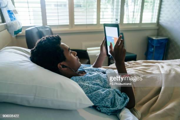 Black boy in hospital bed listening to digital tablet