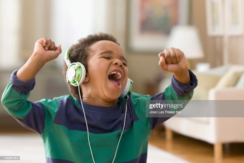 Black boy listening to music on headphones : Stock Photo
