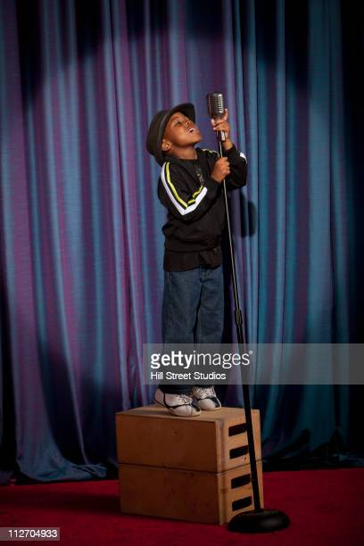 Black boy on crate singing into microphone