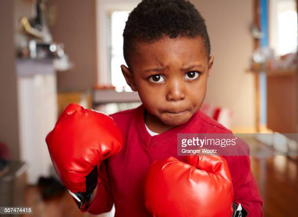 Black boy posing with boxing gloves in living room