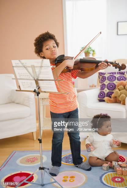 Black boy practicing violin in living room