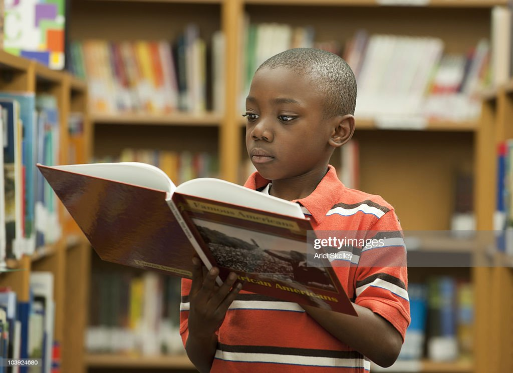 Black boy reading book in library : Stock Photo