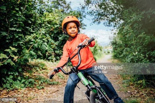 Black boy riding bicycle with helmet