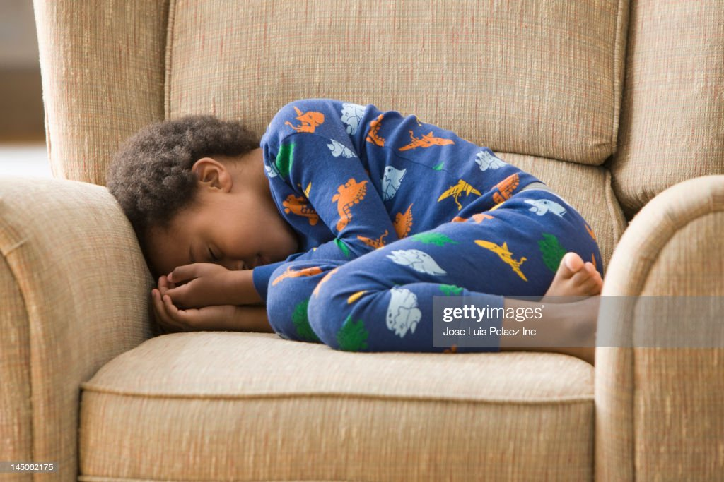 Black boy sleeping in armchair : Stock-Foto